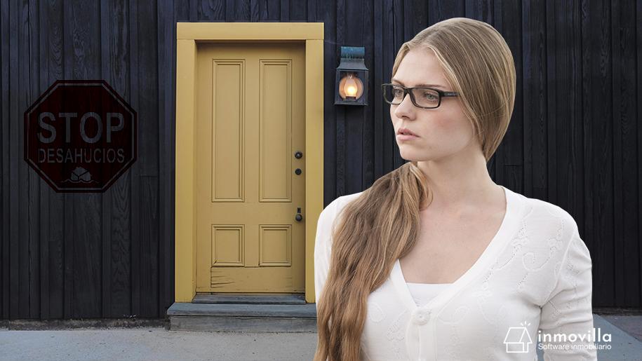 Mujer mirando cartel stop desahucios en una casa